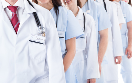 Long line of smiling doctors and nurses